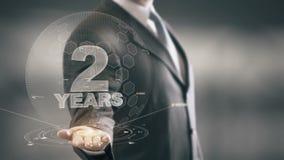 Dos tecnologías disponibles de Holding del hombre de negocios de 2 años nuevas ilustración del vector