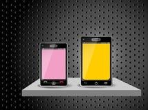 Dos teléfonos elegantes en un estante Foto de archivo libre de regalías