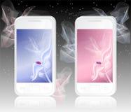 Dos teléfonos móviles blancos con la mariquita en extracto Imagen de archivo libre de regalías