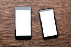 Dos teléfonos móviles en el escritorio de madera Imágenes de archivo libres de regalías