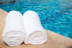 Dos toallas blancas enrolladas por la piscina azul Foto de archivo libre de regalías
