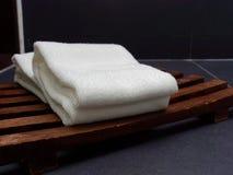 Dos toallas dobladas blanco fueron puestas en la bandeja o la cesta de madera del listón sobre fondo oscuro o negro imagen de archivo