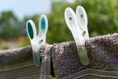 Dos toallas que se secan en una cuerda para tender la ropa con dos pinzas imagen de archivo libre de regalías