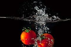 Dos tomates que caen en el agua Fotos de archivo libres de regalías