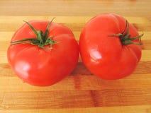 Dos tomates rojos en una tabla de cortar Fotos de archivo libres de regalías