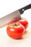 Dos tomates rojos y un cuchillo de acero Fotografía de archivo libre de regalías