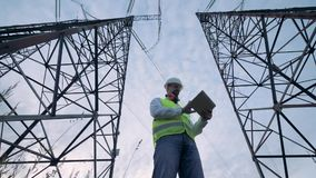 Dos torres altas de la electricidad y un inspector de sexo masculino que trabaja entre ellos almacen de metraje de vídeo