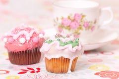 Dos tortas de la taza y tazas de té rosadas Foto de archivo libre de regalías