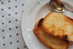 Dos tostadas con la miel en plato Fotos de archivo