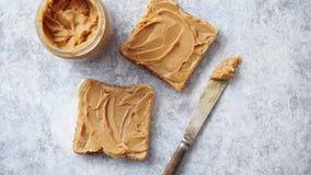 Dos tostadas sabrosas de la mantequilla de cacahuete puestas en la tabla de piedra