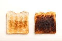 Dos tostaron rebanadas de pan, perfecto y quemado Fotografía de archivo libre de regalías