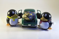 Dos Toy Penguins con el ornamento del día de fiesta en el camión Foto de archivo