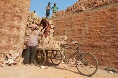 Dos trabajadores cargan la bicicleta con los ladrillos n Dacca, Bangladesh Imagenes de archivo