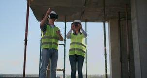 Dos trabajadores contemporáneos del equipo que usan VR para visualizar los proyectos que se colocan en el edificio inacabado en e almacen de video