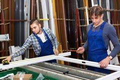 Dos trabajadores cuidadosos que examinan ventanas foto de archivo libre de regalías