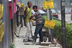 Dos trabajadores de construcción de sexo masculino en el trabajo Foto de archivo libre de regalías