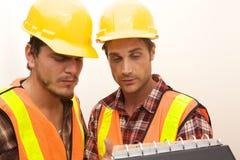 Dos trabajadores de construcción en el trabajo Fotos de archivo