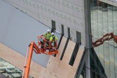 Dos trabajadores de construcción en la elevación con la reflexión Imagen de archivo libre de regalías