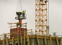 Dos trabajadores de construcción en la ropa fluorescente de la seguridad, colocándose encima de un tejado Imagenes de archivo