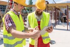 Dos trabajadores de construcción jovenes que sonríen mientras que usa un duri de la tableta foto de archivo