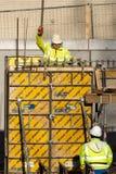 Dos trabajadores de construcción ponen un embarque con grúa con telecontrol fotos de archivo