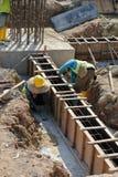 Dos trabajadores de construcción que fabrican encofrado del haz de tierra Imagenes de archivo