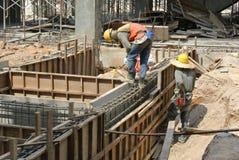 Dos trabajadores de construcción que instalan encofrado del haz de tierra Imagen de archivo libre de regalías