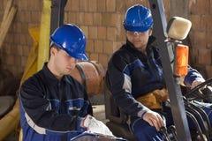 Dos trabajadores de construcción que miran plan Imagen de archivo
