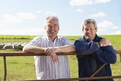 Dos trabajadores de granja con la multitud de ovejas Fotos de archivo libres de regalías