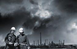 Dos trabajadores de la industria y refinería de petróleo distante foto de archivo libre de regalías