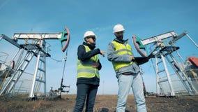 Dos trabajadores de sexo masculino están hablando delante de aceite-torres de perforación de funcionamiento Energía, aceite, gas, almacen de metraje de vídeo