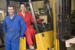 Dos trabajadores del almacén con la carretilla elevadora Fotos de archivo libres de regalías