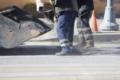 Dos trabajadores del camino en guardapolvos son asperjan un hoyo en el camino con la miga del asfalto antes de nivelar al reparar imagen de archivo