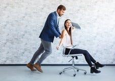 Dos trabajadores del ffice que se divierten en el trabajo, individuo que rueda a una muchacha en una silla en las ruedas Fotos de archivo