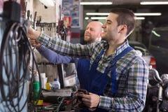 Dos trabajadores del garaje acercan a instalaciones Foto de archivo libre de regalías