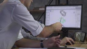 Dos trabajadores discuten el plan arquitectónico en el ordenador, señalando el lápiz al detalle almacen de metraje de vídeo