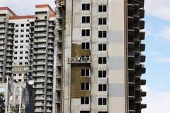 dos trabajadores en cuna suspendida frente en un edificio alto nuevamente construido foto de archivo libre de regalías