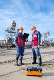 Dos trabajadores en el campo petrolífero foto de archivo