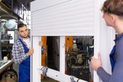 Dos trabajadores en el uniforme que examina ventanas con el obturador Imagen de archivo