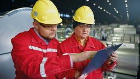 Dos trabajadores en la instalación de producción como equipo que discute, escena industrial en fondo metrajes