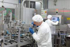 dos trabajadores en la cadena de producción en planta Imagen de archivo libre de regalías