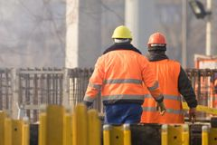 Dos trabajadores en naranja en el área de la reconstrucción foto de archivo libre de regalías
