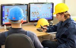 Dos trabajadores en una sala de mando imagen de archivo libre de regalías