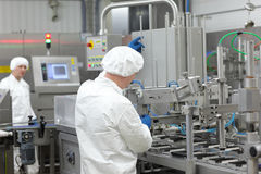 Dos trabajadores en uniformes en la cadena de producción en planta Imagen de archivo