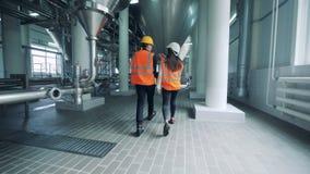 Dos trabajadores están caminando a lo largo de la unidad de la cervecería almacen de video