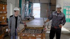 Dos trabajadores están sosteniendo una caja de la ejecución con los detalles acabados del metal, caminando en un espacio del tall almacen de video