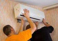 Dos trabajadores instalan el acondicionador de aire en el apartamento fotografía de archivo libre de regalías