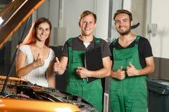 Dos trabajadores jovenes del servicio del coche, y una demostración hermosa o de la chica joven imagen de archivo libre de regalías