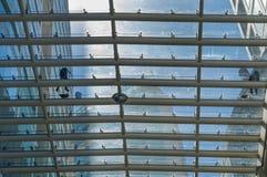 Dos trabajadores limpian el tejado de cristal de un centro comercial en México foto de archivo libre de regalías