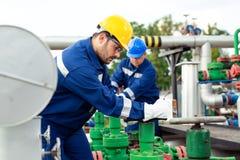 Dos trabajadores petroquímicos que examinan las válvulas de presión en un depósito de gasolina fotos de archivo